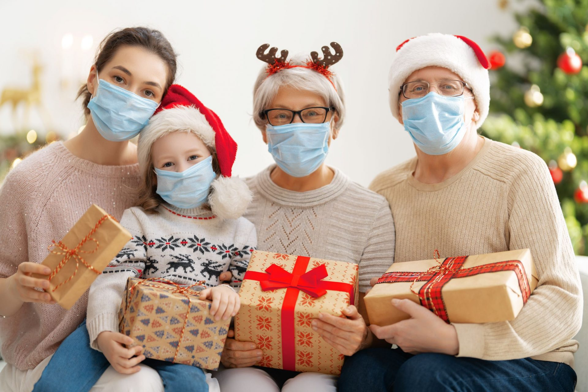 Perhe maskit kasvoilla ja joululahjat sylissä.