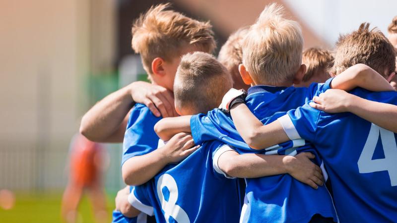 Jalkapallo pojat halaavat toisiaan.