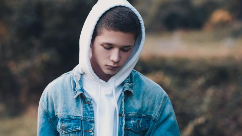 Poika syksyisessä maisemassa seisoo kameraan päin kasvot ja katse kohti maata. Yllään hänellä on farkkutakki ja huppari, jonka hupun poika on vetänyt päähänsä.