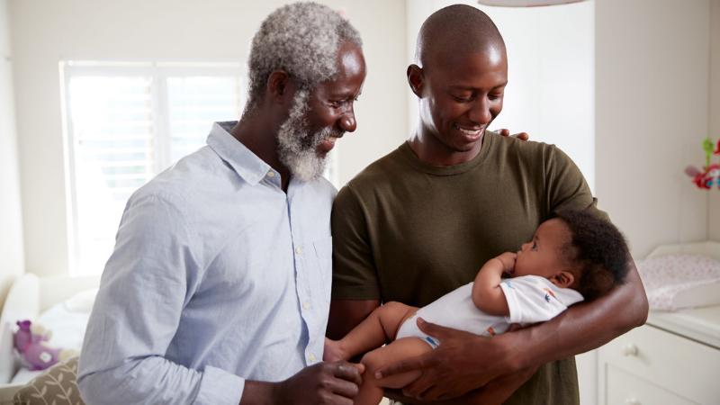 Isä pitää pientä lastaan sylissään, ja tämän isoisä ihailee vieressä.
