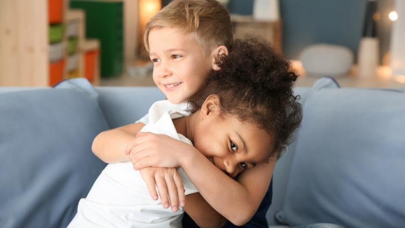 Lapset halaavat sohvalla toisiaan