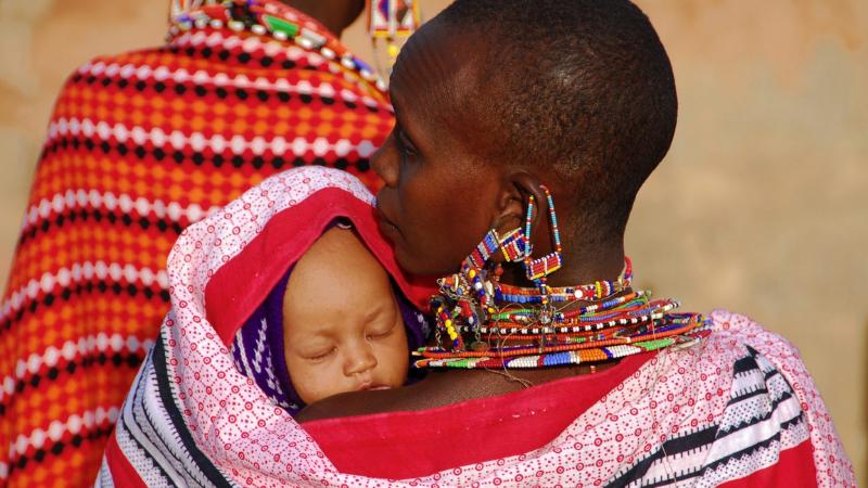 Vauva kanstoliinassa äidin sylissä, ehkä Afrikassa.