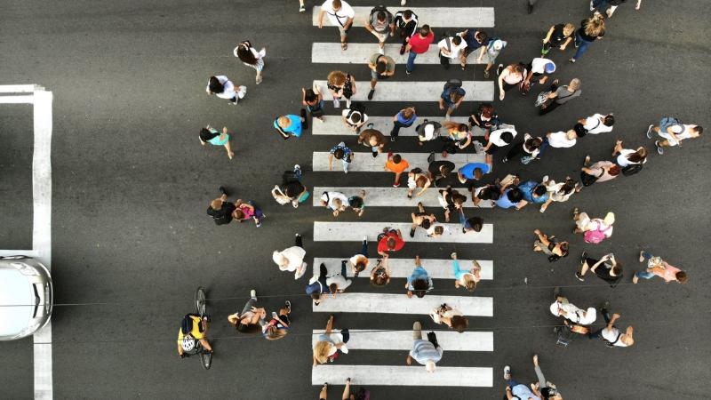 Lintuperspektiivistä otettu kuva, jossa joukko ihmisiä ylittää suojatietä.
