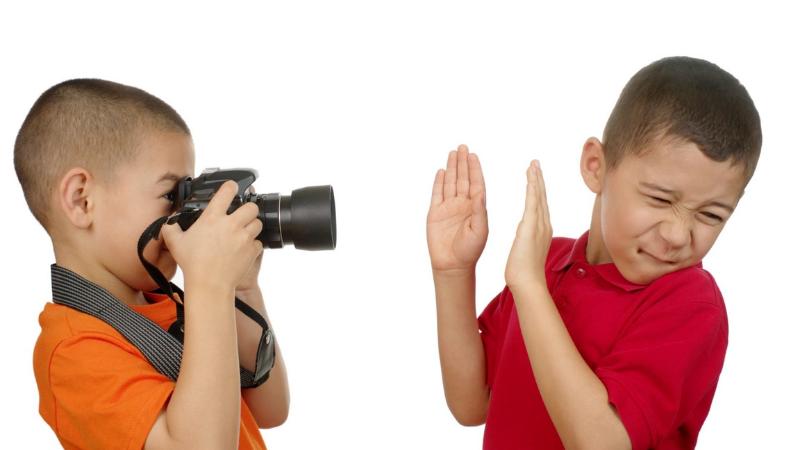 Toinen lapsi kuvaa toista lasta. Lapsi ei halua, että häntä kuvataan.