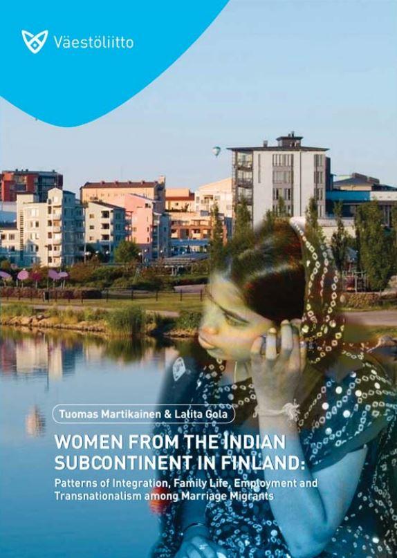 Intialainen nainen maiseman edessä, jossa on taloja veden äärellä.