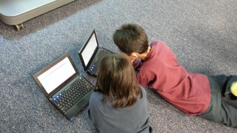 kaksi poikaa tietokoneillaan samalla maassa makuullaan.