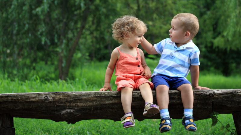 Kaksi lasta istuu penkillä