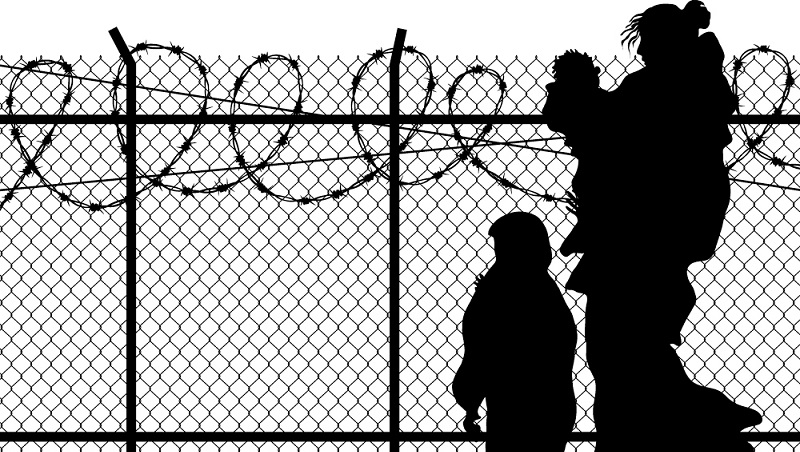silhouette of refugee woman with two children. in front of spike fence