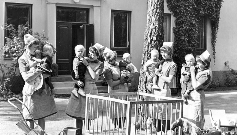 Ryhmä kotisisaropiskelijoita lasten kanssa.