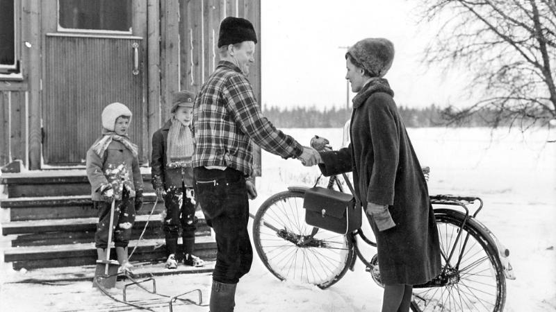 Kotisisar tulee perheeseen, isä ja palset portailla vastassa.