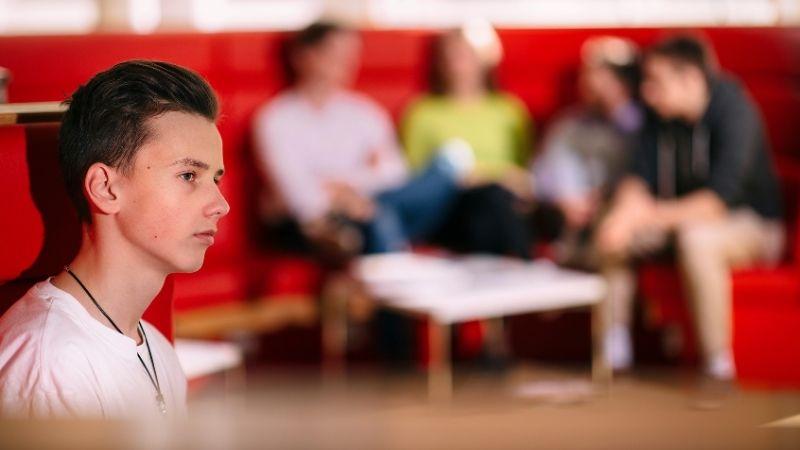 Pojan siluetti, hän katsoo etäisyyteen ja taustalla näkyy hämärästi ryhmä muita nuoria.