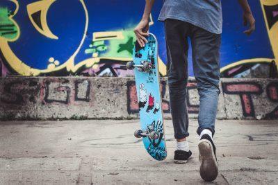 Pojke, fotograferad bakifrån, med en skateboard i vänstra handen, går mot skaterampen.