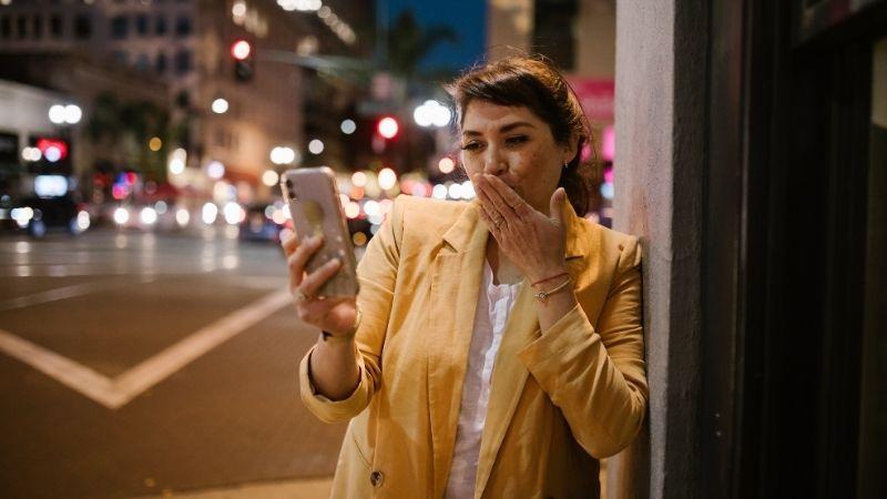 Nainen kännykällä lähettää suukon vastaanottajalle, kyseessä ehkä etäsuhde.