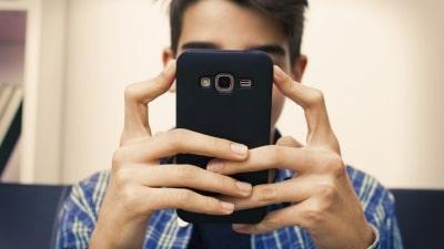 En pojke ser på sin telefon, den döljer hans ansikte