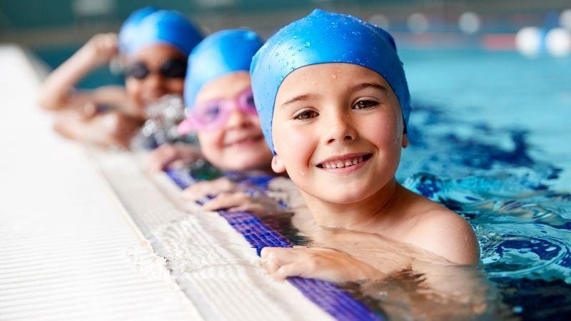 Uintiryhmän tyttöjä uintilakit päässä altaan päässä.