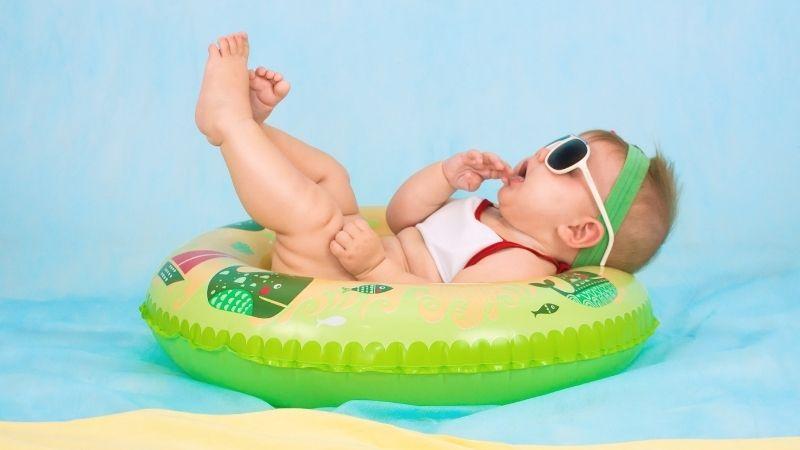 Pieni lapsi makaa selällään uimarenkaassa, bodi ja aurinkolasit päällä ja katselee jalkojaan.