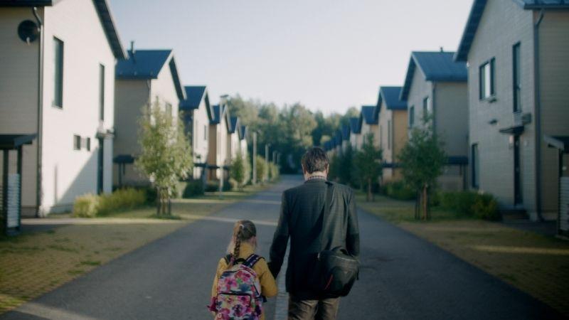 Isä ja lapsi selin kameraan kävelemässä käsikkäin kotitiellä.