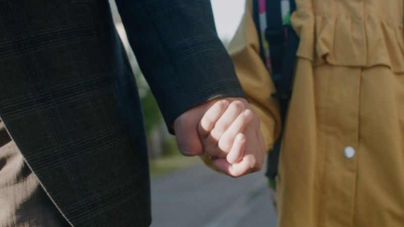 Aikuisen ja lapsen kädet on kuvattu läheltä, kun he kävelevät käsi kädessä.