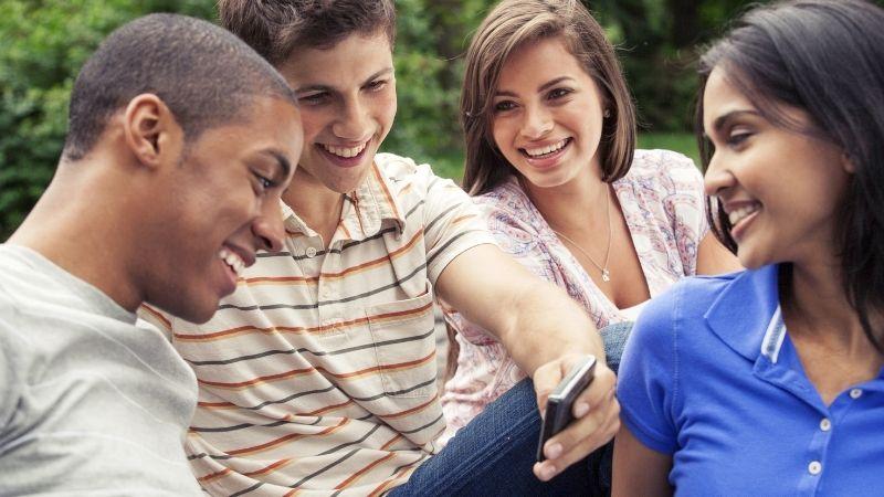 Neljä nuorte istuu yhdessä iloisen näköisenä.