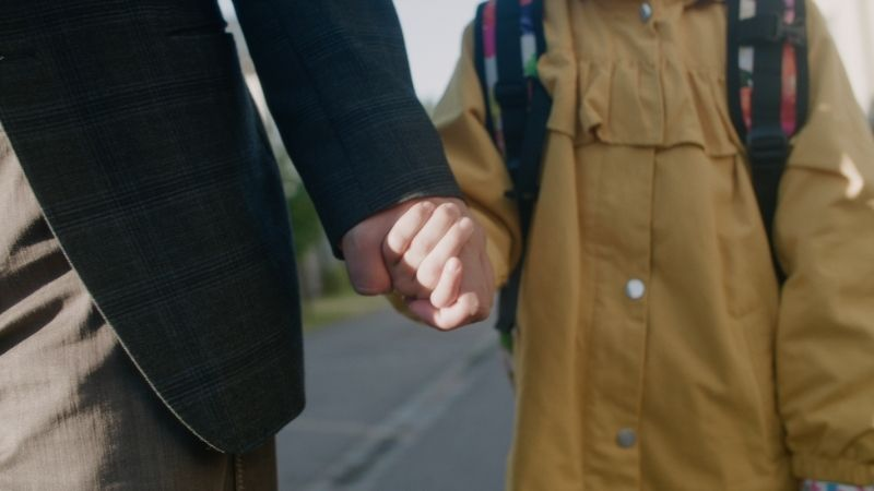 A parent and a child holding hands and wearing autumn clothes.