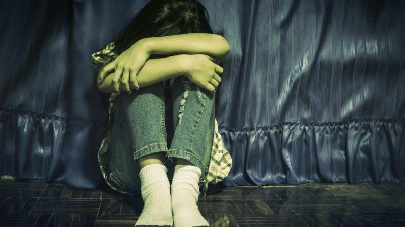 Nuori surullimem tai ahdistunut tyttö istuu kippurassa pää polvissa.