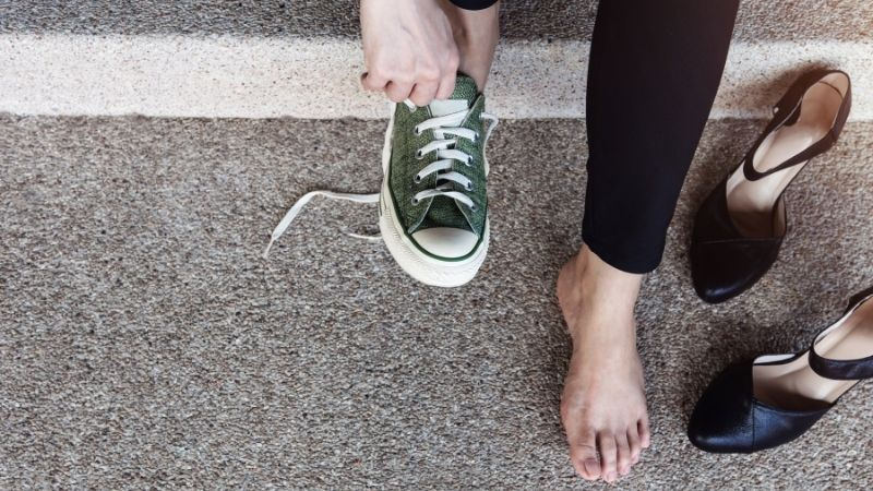 A Woman changing from working shoes to sneakers.
