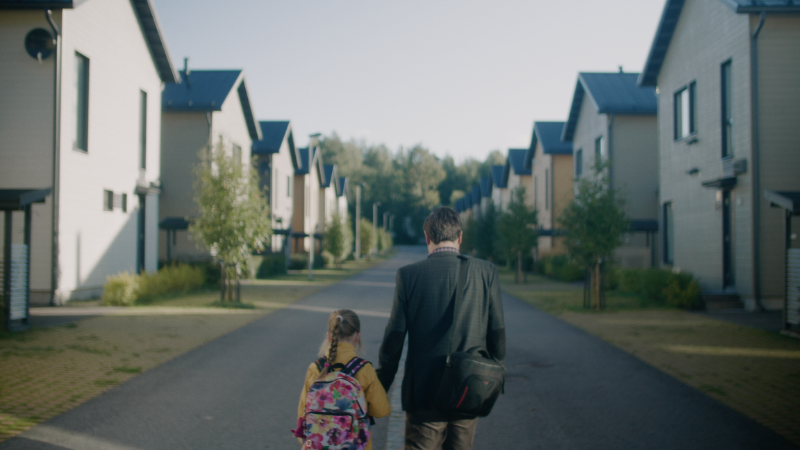 A father and a child walking hand in hand.
