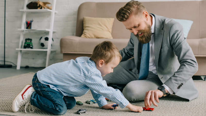 A father is playing with a child on the floor.